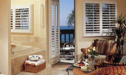 Plantation shutters on casement windows in a beachfront home.
