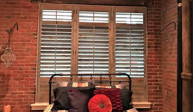 Reclaimed wood shutters next to brick wall.
