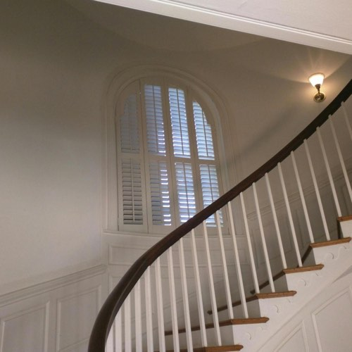 White plantation shutters covering rounded window located in curved stairwell.